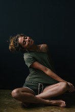 Young Woman Stretches In A Dark Room
