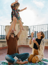 Stylish Parents Playing With Girl On Terrace