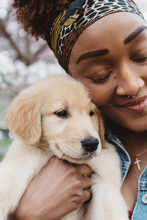 A Black Woman In Her Twenties Holding Her Golden Retriever Puppy Dog