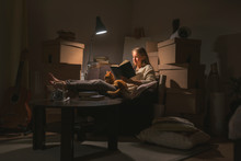 Young Woman Reading Book At Home