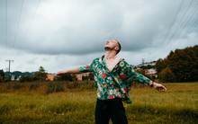 Handsome Man In A Green Floral Blouse Enjoys In The Field