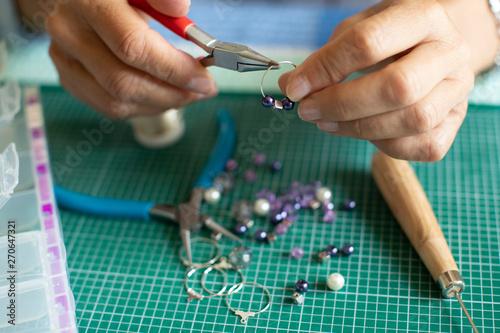 Close Up Of Senior Woman Making Jewellery Earrings At Home Fototapet