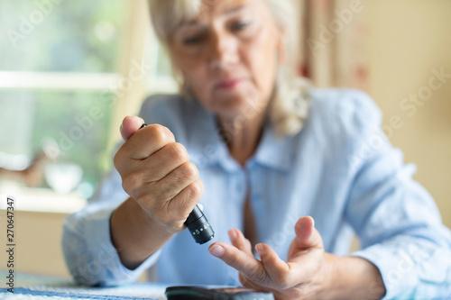 Fotomural  Senior Woman Testing Blood Sugar Level At Home