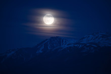Moon Rising Behind The Peak Of Snow Covered Mountain