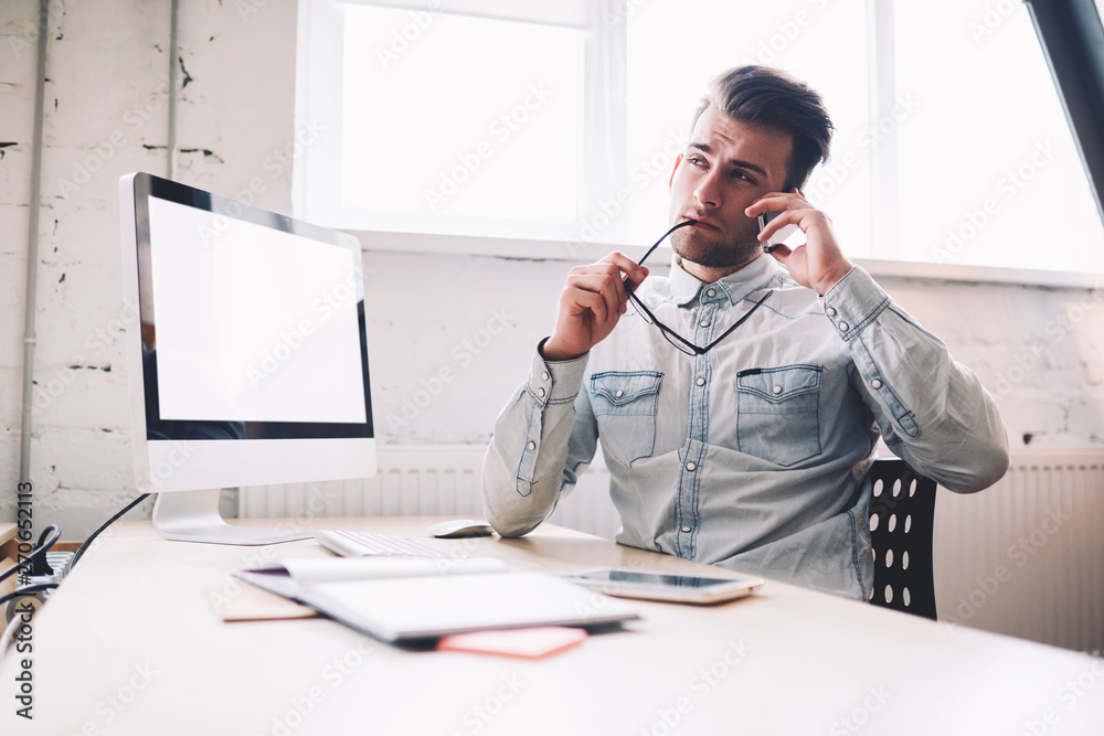 Fototapety, obrazy: Young contemplative male copywriter pondering on information received from important telephone call, modern computer with blank screen for your internet advertising staying on desktop in office