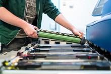 Close-up Of Teenager Working At Color Printer Inserting Print Cartridge