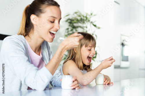 Fototapeta Beautiful young mother and her daughter eating iogurt at home. obraz