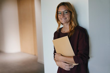 Smiling Businesswoman Leaning Against A Wall Holding Folder