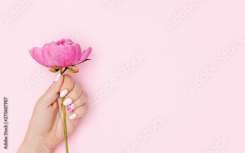 Aluminium Prints Manicure Woman hand with trendy nail art manicure holding peony flower on pink background