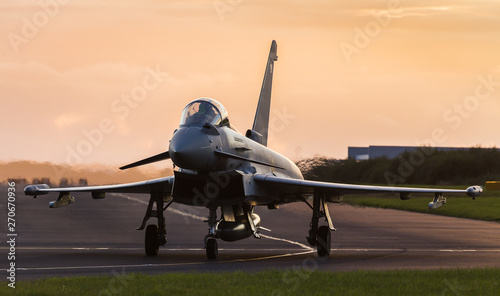 Fotografie, Obraz Backlit Typhoon taxis out for takeoff