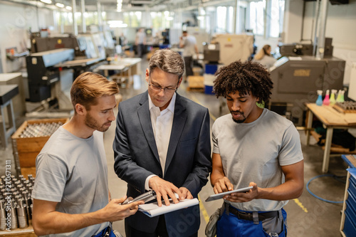 Photo  Young metal workers cooperating with their manager while reading reports in a factory