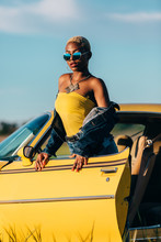 Beautiful African Woman Leaning To A Classic Yellow Car
