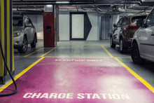 Electric Car Charging Station In Underground Indoor Parking Of Mall Or Office Building. Reserved Parking Lot For Environment Friendly Green Energy Zero Emiision Vehicles With Fast Charger Plugs