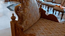Traditional Carved Wooden Armchair Trimmed With Yellow Fabric With Patterns In The Indian Style. Shot In Motion