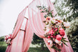 canvas print picture - wedding ceremony in nature. arch decorated with a pink cloth. rows of wooden chairs.