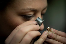 Close-up Of Female Goldsmith Examining Gold Through Loupe At Workshop