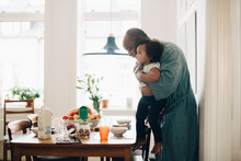 Father Making Daughter Sit At Table For Breakfast In Dining Room