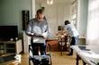 Retired senior man reading newspaper while female caregiver working in kitchen at nursing home