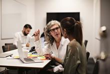Kvinnor Diskuterar Vid Laptop I Konferensrum Med Kollegor I Bakgrunden