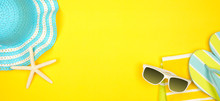 Beach Accessories On A Yellow Background. Summer Vacation Concept Banner With Copy Space. Sunglasses, Sea Shells, Towel, Flip Flops And Blue Striped Hat.