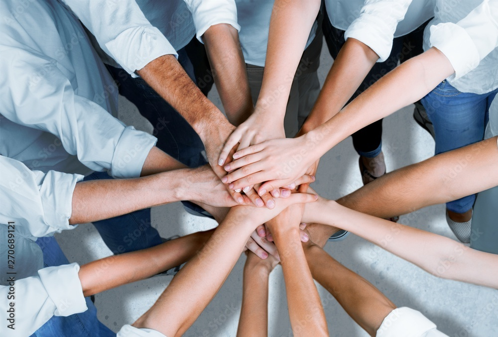 Fototapeta Group of people stacking hands together