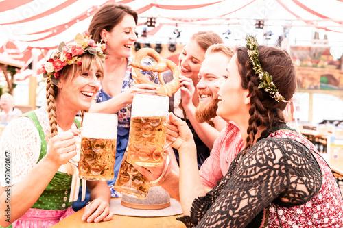 Fototapeta Gruppe von Freunden am Biertisch stoßen mit Maß an und lachen und flirten auf de