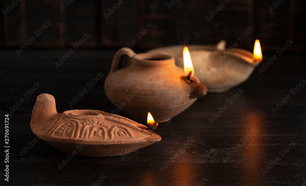 Fototapety, obrazy: Lit Handmade Oil Lamp from the Middle East on a Dark Table
