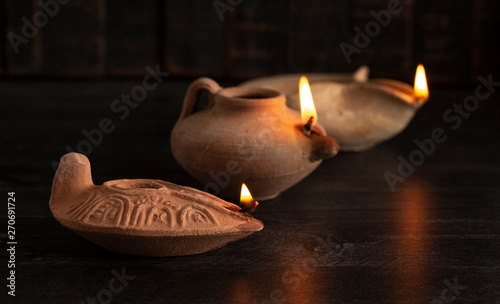 Fotografiet  Lit Handmade Oil Lamp from the Middle East on a Dark Table