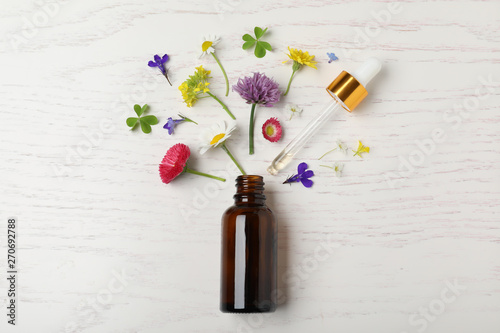 Photo  Bottle of essential oil and different flowers on white wooden background, flat l