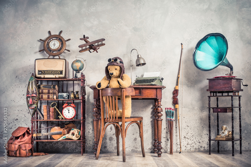 Fototapety, obrazy: Teddy Bear toy on chair, typewriter, vintage gramophone, old books, radio, globe, binoculars, carnival mask, camera, fiddle on shelf, steering wheel, plane, travel backpack, bow. Retro style photo