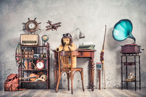 Photo Stands Music store Teddy Bear toy on chair, typewriter, vintage gramophone, old books, radio, globe, binoculars, carnival mask, camera, fiddle on shelf, steering wheel, plane, travel backpack, bow. Retro style photo