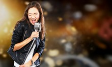Young Woman Singing With Microphone On Blurred Background