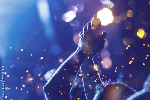 Audience with hands raised at a music festival and lights streaming down from above the stage. Soft focus, blurred movement. - 270698398