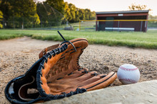 Baseball And Glove On Pitchers Mound On Early Morning Springtime