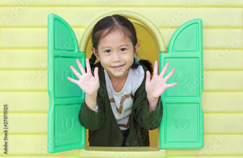 Fototapeta Happy little Asian child girl playing with window toy playhouse in playground