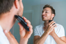 Young Man Shaving Neck And Jawline In The Morning Using Electric Shaver / Clipper. Morning Routine Modern Lifestyle. Male Beauty 30s Model.