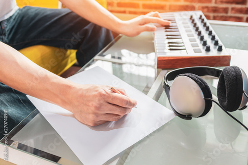 Photo male songwriter playing music keyboard and writing a song on blank white paper,