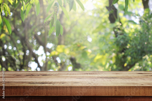 Wooden empty and blurred fresh green nature garden background.