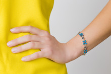 Woman In Yellow, Bright Clothes On Gray Background. Hand On Hips. Blue Flower Bracelet On Wrist. Daily Beauty. Part Of Body. Closeup. Front View.