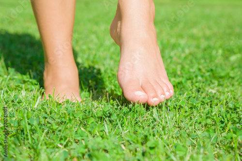Obraz na plátně Young woman barefoot walking on fresh, green grass in sunny summer in morning