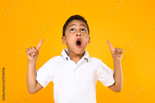 Fotografiet  Portrait of cute little boy pointing at something on color background