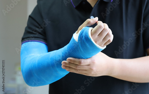 Foto  Closeup of asian man's arm with long arm plaster, fiberglass cast therapy cover by blue elastic bandage after sport injury