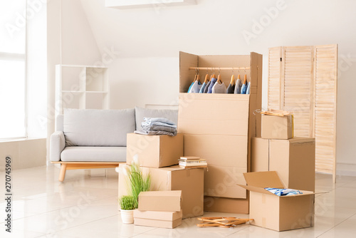 Photo Wardrobe boxes with clothes and other things prepared for house moving in room