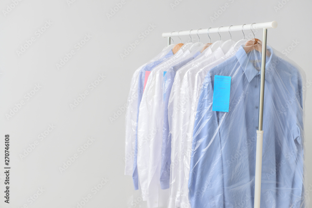 Fototapeta Rack with clothes after dry-cleaning on light background