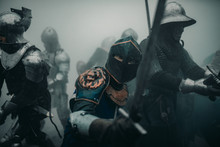 Squad Of Medieval Knights Of The Crusaders During The Battle With Swords In Misty Morning.
