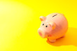 Happy piggy bank on yellow background, space for text. Finance, saving money