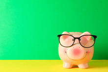 Happy Piggy Bank With Glasses On Color Table Against Green Background, Space For Text. Finance, Saving Money