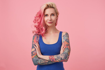 Portrait of positive cute lady with pink hair and tattooed hands, standing over pink background and smiling, wearing a blue shirt. People and emotion concept.