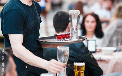 Fotografie, Obraz  Waiter with tray takes empty beer glasses and brings cocktails to the guests of restaurant on the summer terrace