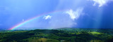 Fototapeta Tęcza - Impressive view at the tropical tableland with a colourful rainbow during rainseason.A heavy tropical rain falling down on the forests and valleys. Millaa Millaa Lookout,Far North Queensland,Australia